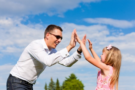 Family affairs - father and daughter playing in summer; he is dancing with her while having a walk photo