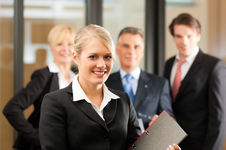 female lawyer: Business - team in an office, the junior manager is standing in front Stock Photo