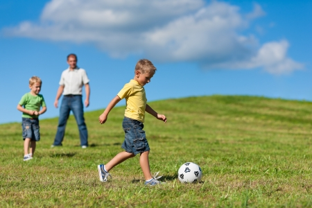 father with child: Happy family is playing soccer in summer in a beautiful landscape Stock Photo