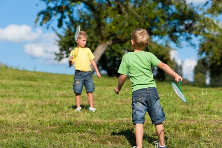 Family - two little boys playing badminton outdoors on a summer day photo