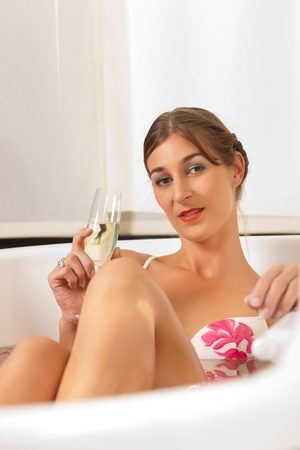 wife of bath: Wellness and Spa - young beautiful woman is enjoying a glass of champagne in bathtub