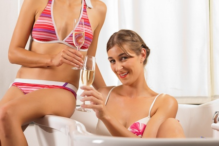 wife of bath: Wellness and Spa - young beautiful woman with her female friend is enjoying a glass of champagne in bathtub Stock Photo