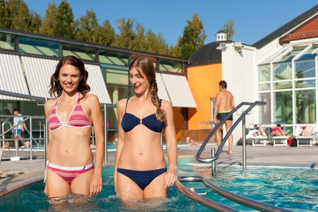 Two happy young women walking into the water of a swimming pool; they are wearing a bikini photo
