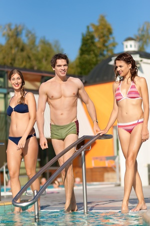 Two happy young women and a man - friends - walking into the water of a swimming pool; they are wearing swimwear photo