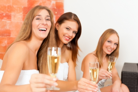 Wellness - young, happy female friends drinking champagne in spa and have fun photo