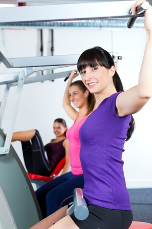 Happy, young women doing strength or sports training in gym for a better fitness Stock Photo - 13319439