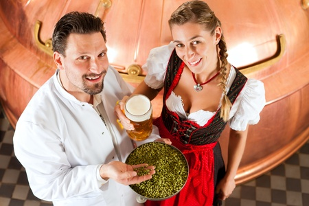 brewer: La mujer y su cerveza masculino con jarra de cerveza y el l�pulo en su f�brica de cerveza Foto de archivo