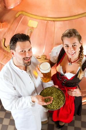 beer production: Woman in Tracht and brewer with beer stein and hops in her brewery