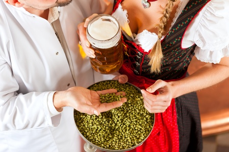 brewer: Mujer en Tracht y cervecero, con jarra de cerveza y el l�pulo en su f�brica de cerveza
