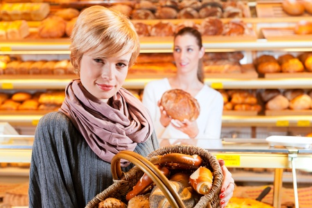 Female baker or saleswoman in her bakery with a female customer and fresh pastries or bakery products Stock Photo - 13319644