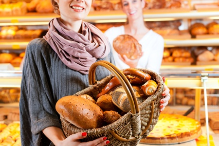 bakery store: Female baker or saleswoman in her bakery with a female customer and fresh pastries or bakery products