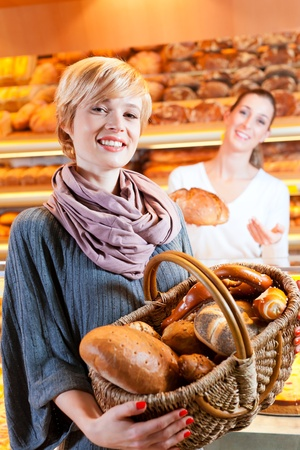 Female baker or saleswoman in her bakery with a female customer and fresh pastries or bakery products photo