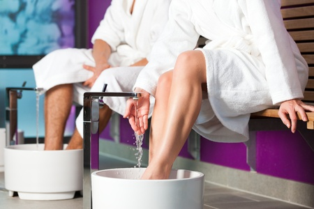 Couple - man and woman - having hydrotherapy water footbath in spa setting photo