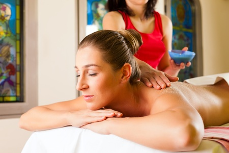 Woman receiving a massage in wellness spa by a masseuse photo