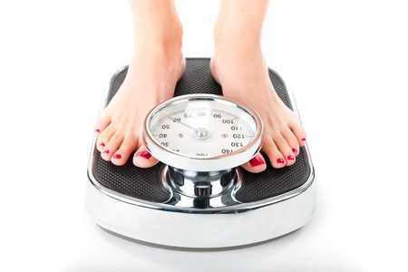 bulimia: Diet and weight, young woman standing on a scale, only feet to be seen