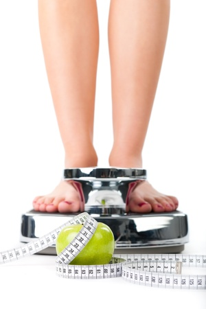 BMI: Diet and weight, young woman standing on a scale, only feet to be seen, a apple and a measuring tape