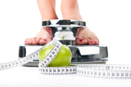 scale: Diet and weight, young woman standing on a scale, only feet to be seen, a apple and a measuring tape