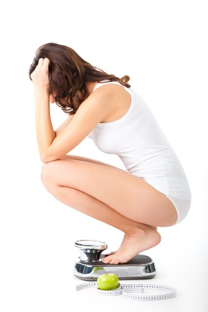 anorexia girl: Diet and weight, young woman sitting on her haunches on a scale with apple and measuring tape