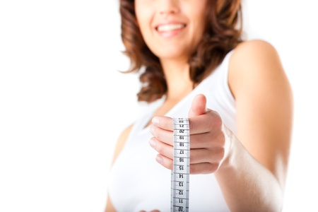 Diet and weight, young woman with a measuring tape for controlling her measure photo