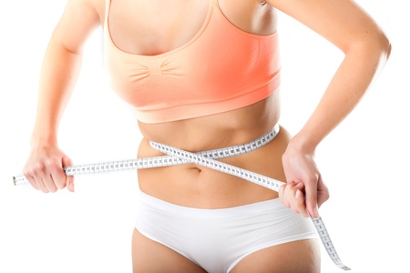 ideal: Diet - young woman is measuring her waist with measuring tape Stock Photo