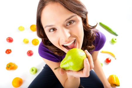Healthy eating, happy woman with fruits and vegetables is eating a pear  Stock Photo - 13319283