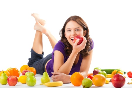 Healthy eating, happy woman with fruits and vegetables is eating a apple Stock Photo - 13319260