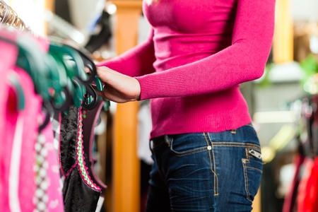 clothing rack: Traditional clothes - A young woman is buying Tracht or dirndl in a shop, cropped image Stock Photo