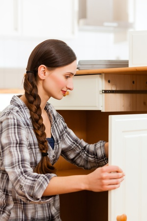 out door: Young woman is assembling a cupboard because she is moving in or out Stock Photo