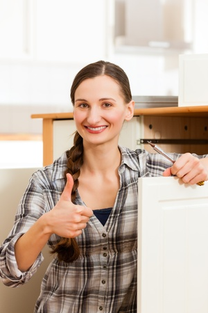 assembling: Young woman is assembling a cupboard because she is moving in or out - thumps up