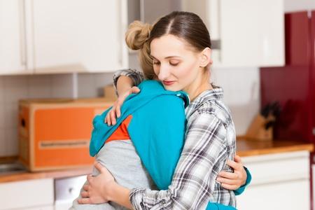 uitpakken: Twee gelukkige vrouwelijke vrienden te bewegen in een appartement, ze omhelzen elkaar, omdat alles in het werk Stockfoto