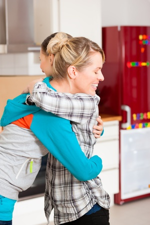 Two happy female friends moving in an apartment, they hug each other since everything is done photo