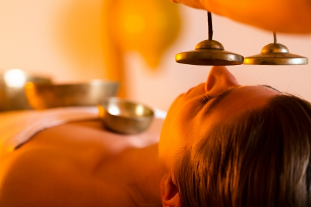Woman in wellness and spa setting having a singing bowl massage therapy, the therapist is waking her up with cymbals Stock Photo - 13319485