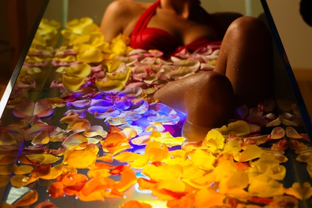 Woman bathing in spa with color therapy, the bathtub is lit with colorful lights, lots of flower petals on tub Stock Photo - 13319266