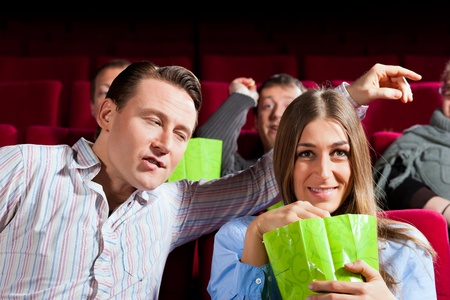 Couple in cinema watching a movie, they eating popcorn Stock Photo - 13453048