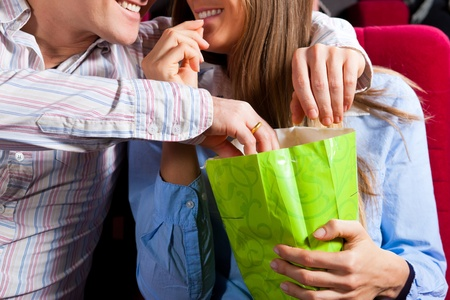 they are watching: Couple in cinema theater watching a movie, they eating popcorn, close-up
