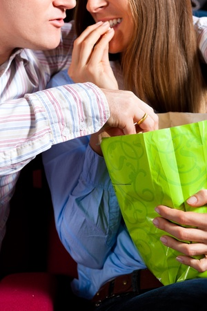 Couple in cinema theater watching a movie, they eating popcorn, close-up Stock Photo - 13453009
