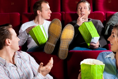 they are watching: Five people - amongst them a couple - in cinema theater watching a movie, they eating popcorn