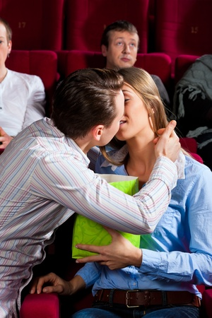 Couple in cinema watching a movie, they eating popcorn and kissing photo