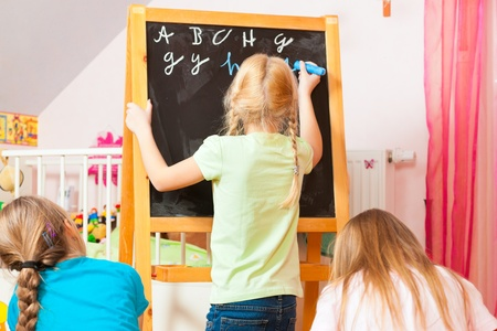 Children - sisters - playing school in their room Stock Photo - 13452903