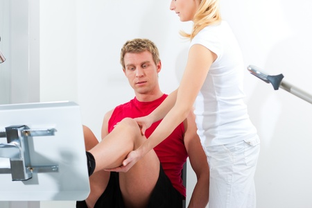 female therapist: Patient at the physiotherapy making physical exercises with his therapist