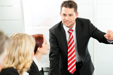 convincing: Business - presentation within a team, a colleague is explaining the strategy Stock Photo