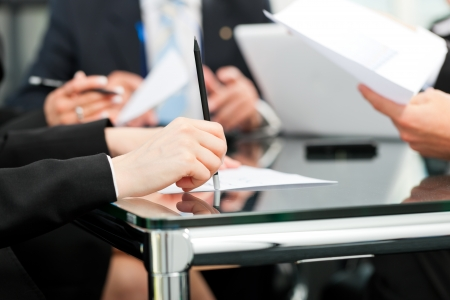 law business: Business - meeting in an office, lawyers or attorneys discussing a document or contract agreement Stock Photo