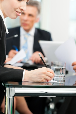 business law: Business - meeting in an office, lawyers or attorneys discussing a document or contract agreement Stock Photo