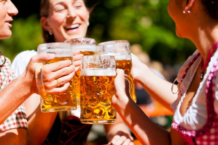 stein: Two happy couples sitting in Bavarian Beer garden and enjoy the beer and the sun