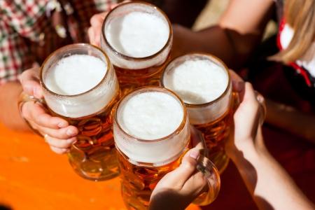 man drinkt bier: Vier vrienden met een frisse pint in een biertuin, close-up op bier stein Stockfoto