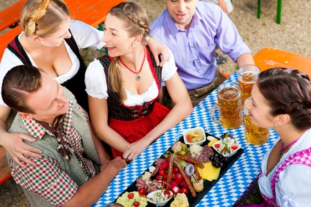 stein: In Beer garden - friends Tracht, Dirndl and on a table with beer and snacks in Bavaria, Germany Stock Photo