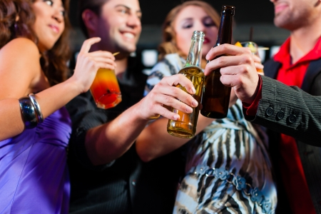 two couples: Group of party people - here two couples - with cocktails and beer in a bar or club having fun Stock Photo