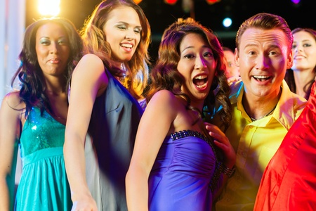 nightclub crowd: Group of party people - a man and women - dancing in a disco club to the music