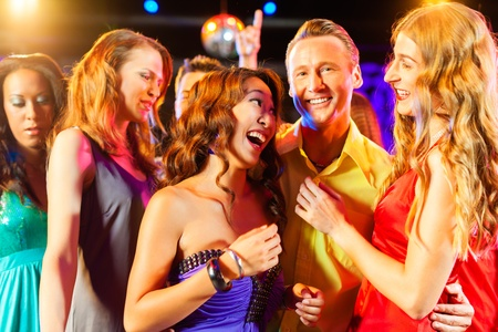 Group of party people - a man and women - dancing in a disco club to the music Stock Photo - 13453052