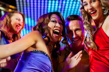 Group of party people - a man and women - dancing in a disco club to the music photo